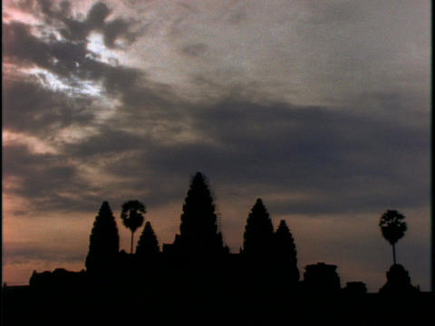Sunlight tries to break through the clouds over Angkor Wat temple in Cambodia during golden hour Footage