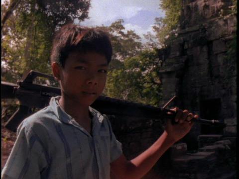 A Khmer Rouge boy holds a gun Stock Video Footage