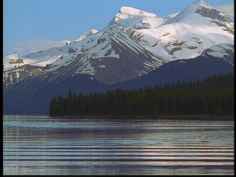 The Canadian Rockies rise above a mountain lake Stock Video Footage