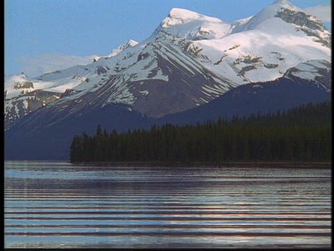 The Canadian Rockies rise above a mountain lake Footage