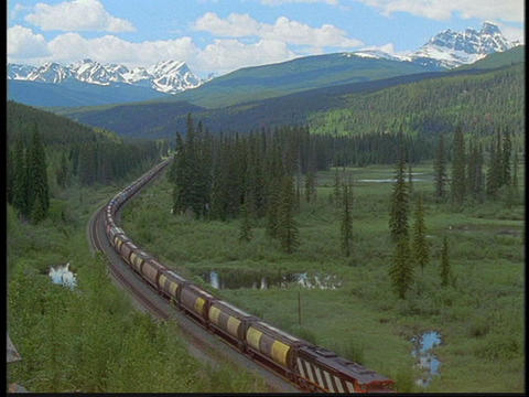 A freight train travels through the Canadian Rockies Stock Video Footage