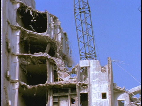 A wrecking ball hits a dilapidated building causing it to... Stock Video Footage