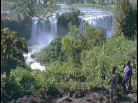 An Ethiopian tribe walks in front of the Blue Nile waterfall Stock Video Footage