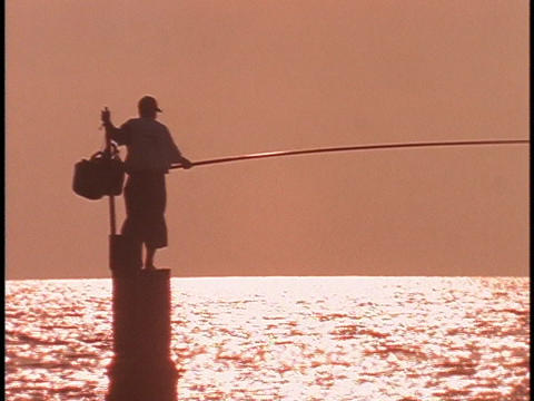 A Fisherman Fishes With A Long Pole stock footage