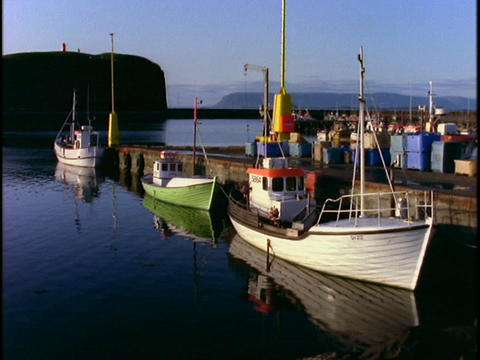 Small fishing boats float beside a dock Stock Video Footage
