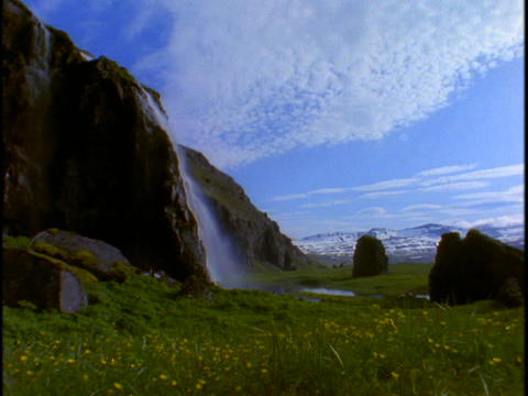 A waterfall tumbles down the face of a mountain Stock Video Footage