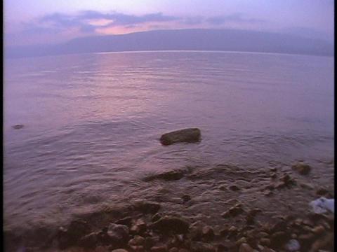 A gentle tide rolls over rocks in the Sea of Galilee Stock Video Footage