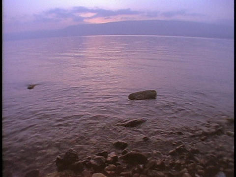 A gentle tide rolls over rocks in the Sea of Galilee Footage