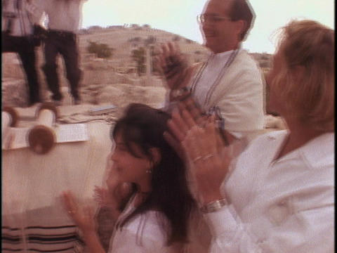 A Rabbi and a young boy dance at a Bar Mitzvah outside... Stock Video Footage