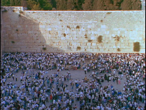 A crowd of people mills about at thee Wailing Wall in Israel Footage