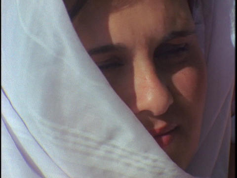 An Arab woman smiles and adjusts her scarf Footage