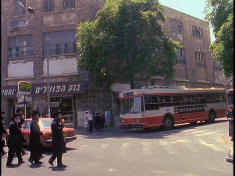 Orthodox Jews walk in street near Mea Shearim, Jerusalem Stock Video Footage