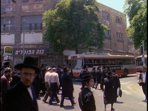 Orthodox Jews walk in street near Mea Shearim, Jerusalem Stock Video Footage