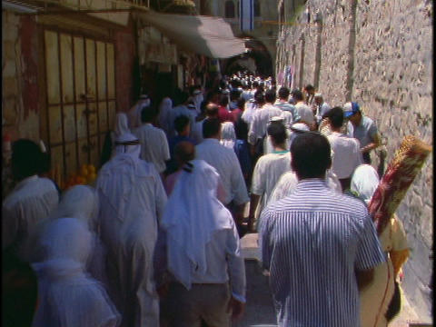 A crowd of Muslim Palestinian people walk in a narrow alley Stock Video Footage