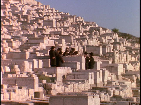 Orthodox Jews stand in a cemetery at the Mount of Olives,... Stock Video Footage