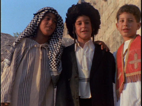 A Muslim, Islamic, and Christian boy link arms and sway... Stock Video Footage