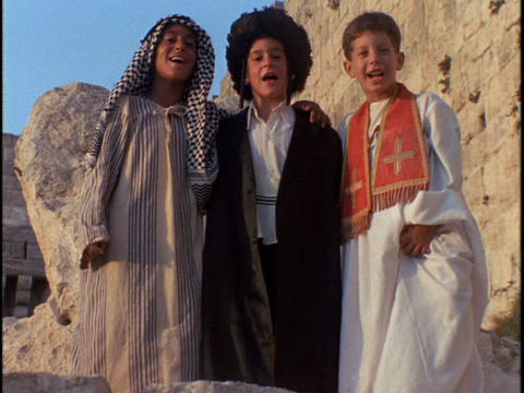 A Muslim, Islamic, and Christian boy link arms and sway together outside Old City Jerusalem Footage
