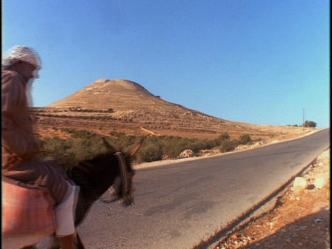 An Arab man rides a donkey down a lonely road Stock Video Footage
