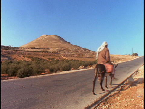 An Arab man rides a donkey down a lonely road Footage