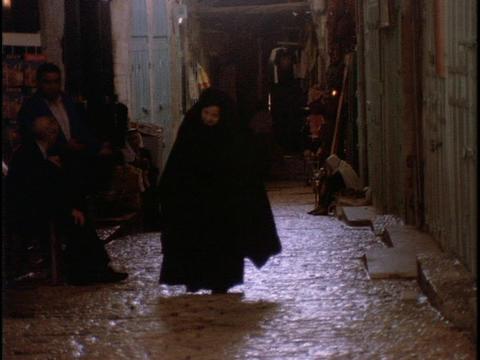 A woman walks on a cobblestone street Stock Video Footage