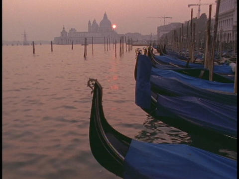 Gondolas lie moored in a Venice harbor Stock Video Footage