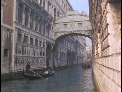 A gondola sails under the Bridge of Sighs in Venice, Italy Footage