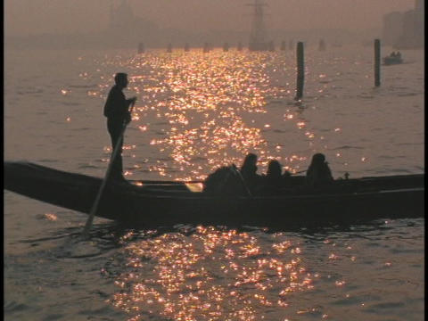 A gondolier in silhouette rows a gondola Stock Video Footage