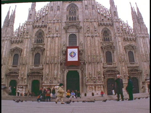 Pigeons fly in the courtyard in front of the Duomo cathedral in Milan, Italy Footage