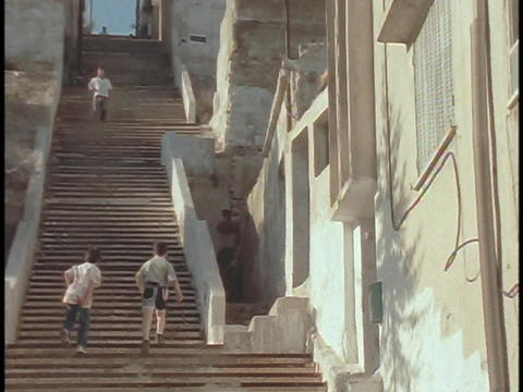A boys walk up steep stairs in a Middle Eastern city Footage