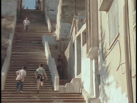A boys walk up steep stairs in a Middle Eastern city Stock Video Footage