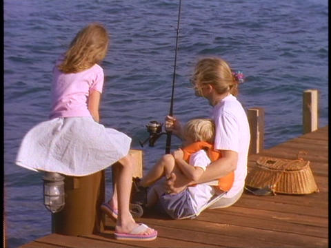 A mother and her children fish off a dock Stock Video Footage