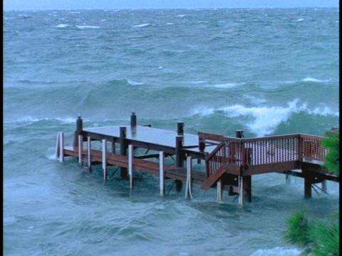 Waves break over dock in a storm Stock Video Footage