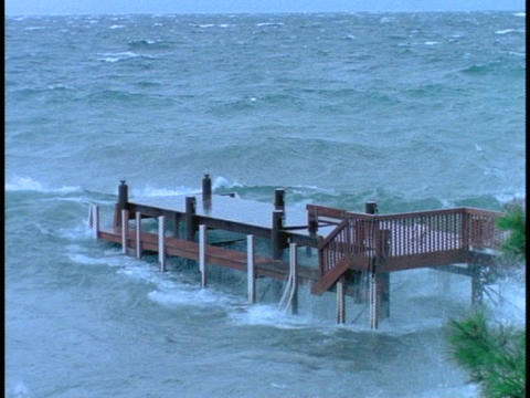 Waves break over dock in a storm Live Action