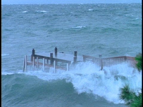 Waves break over dock in a storm Stock Video Footage