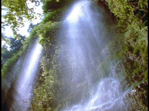 A beautiful tropical waterfall cascades down a cliff Stock Video Footage