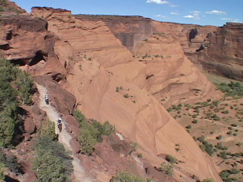 Horses and riders move up a canyon trail Footage