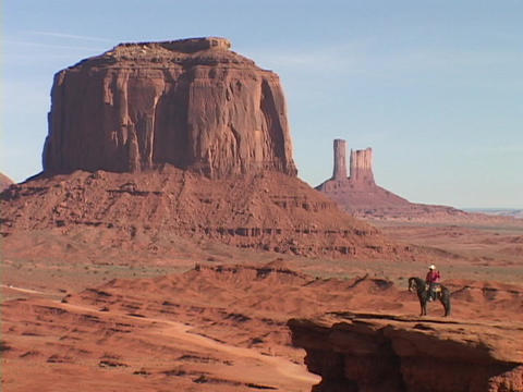 A cowboy on horseback surveys the dramatic scenery of Monument Valley, Utah Footage