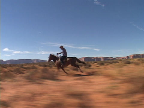 A cowboy on horseback rides fast across the Utah desert Stock Video Footage