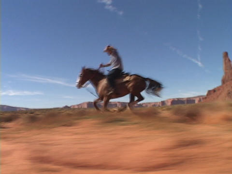A cowboy on horseback rides fast across the Utah desert Footage
