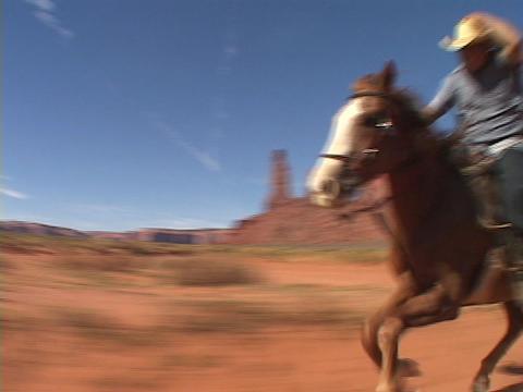 A cowboy on horseback rides fast across the Utah desert Stock Video Footage