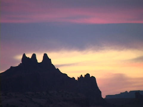 The colorful sky silhouettes rock formations in the Utah desert Footage