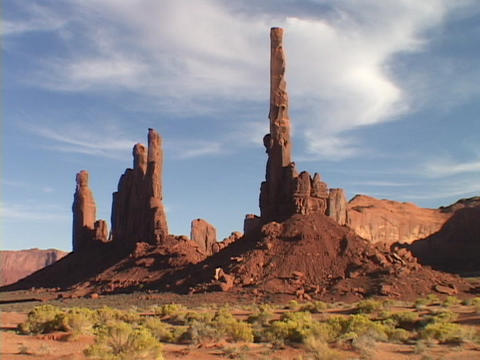 The Totem Pole stands against a blue sky in Monument Valley, Utah Footage