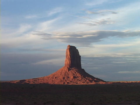 Shadows surround the base of a butte in Monument Valley, Utah Footage