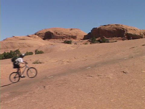 A mountain biker rides across the Moab desert Stock Video Footage
