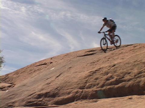 A mountain biker rides across the Moab desert Stock Video Footage