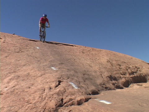 A mountain biker rides down a rocky hill in Moab Footage