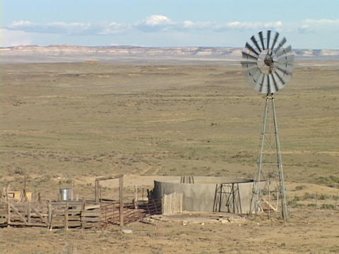 An old windmill and water tank occupy a dry plain Stock Video Footage