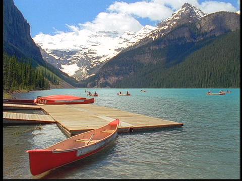 Canoes float beside a dock in scenic Lake Louise Footage
