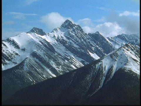 Clouds billow over mountain peaks in the Canadian Rockies Stock Video Footage