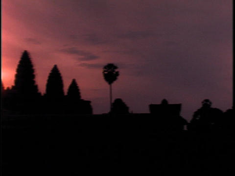 The sky glows orange behind Angkor Wat, Cambodia during the golden hour Footage